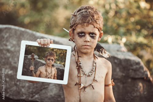 Caveman, manly boy holding tablet PC with his photo on screen. Funny young primitive boy outdoors. Evolution degradation concept. Calm boy outside against rocky background. Prehistoric tribal man