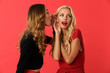 Leinwanddruck Bild - Shocked young friends women standing isolated over red background gossiping.