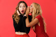 canvas print picture - Amazing shocked young friends women standing isolated over red background.