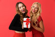 Leinwanddruck Bild - Emotional happy young friends women standing isolated over red background holding gift box surprise.