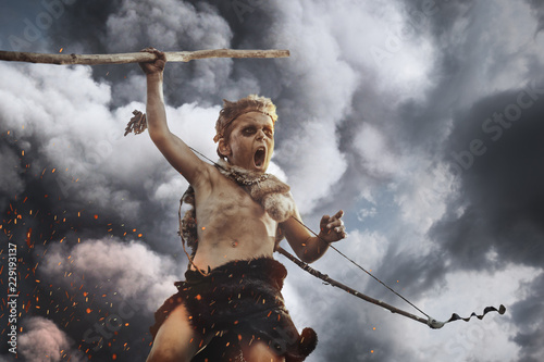 Fotografía  Caveman, manly boy with weapon aggressively shouting