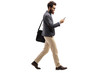 Leinwandbild Motiv Man walking and looking into a mobile phone