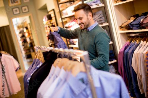 Plakat Portret młody człowiek patrzeje ubrania kupować przy sklepem