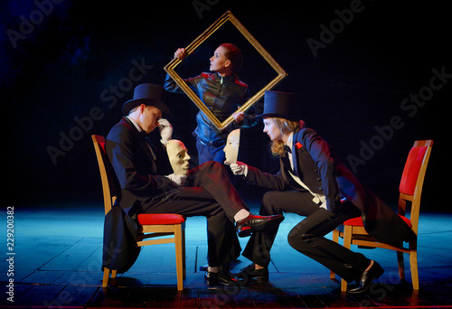 Obraz young actors in tuxedos holding a theatrical mask and picture frame - fototapety do salonu
