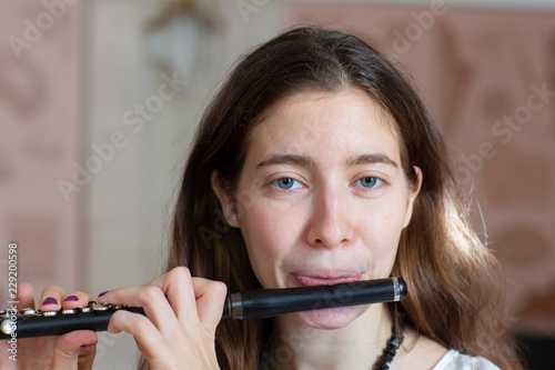 Fotografie, Obraz  A gorgeous young woman sitting and playing the flute piccolo