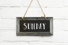 Hello Sunday Weekend Text On Hanging Board White Brick Outdoor Wall
