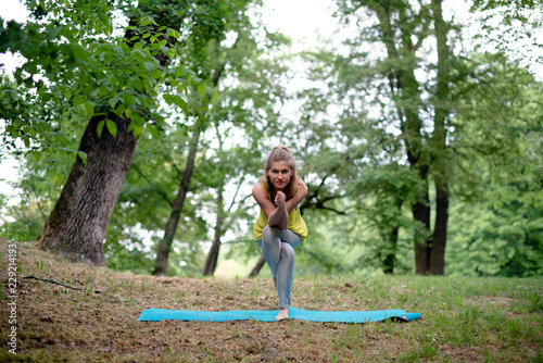 Valokuva  Young woman performing yoga outdoors