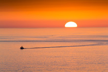 This Fishing Boat Heads Home From Fishing In Front Of A Beautiful Sunset At Clearwater Beach, Florida In The Gulf Of Mexico.