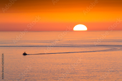 Fotografija This fishing boat heads home from fishing in front of a beautiful sunset at Clearwater Beach, Florida in the Gulf of Mexico