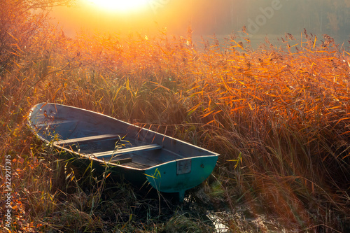 Obraz na plátně Fishing boat in the reeds in the morning at sunrise on the lake