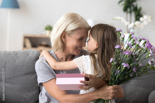 Valokuva  Happy grandmother and granddaughter hug celebrating birthday together, cute litt