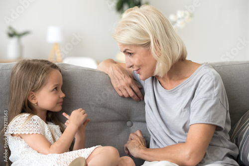 Fotografia  Cute little girl and attentive grandmother sit on couch at home having casual co