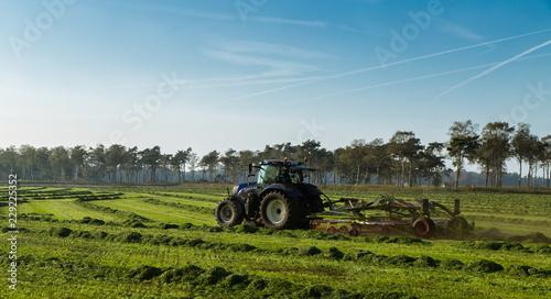 Valokuva  Een boer is met zijn trekker het gemaaide gras aan schudden