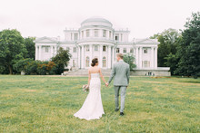 Stylish Wedding In St. Petersburg. Elagin Island And Castle In The Background. Walking Photo Session Of The Couple.