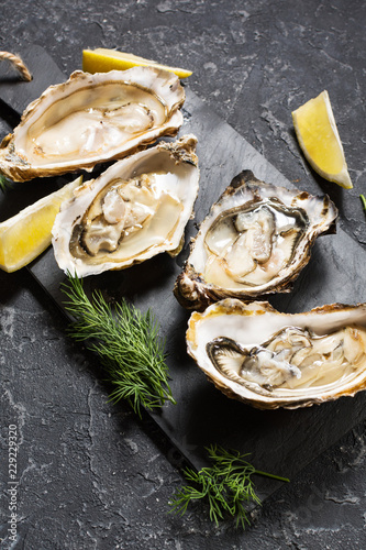 Staande foto Schaaldieren Opened Oysters with lemon on dark stone background