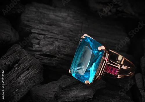 Photo Jewelery ring with aquamarine gemstone on dark coal background, copy space