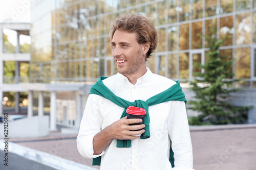 Fotografía  Portrait of handsome young man with cup of coffee on city street