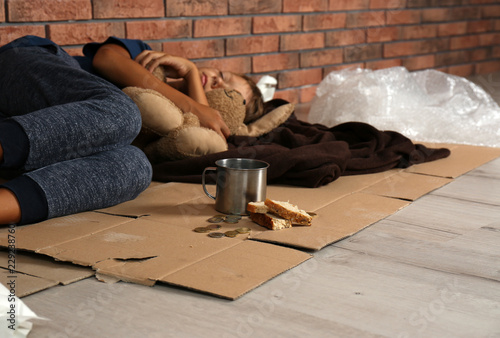 Poor homeless boy sleeping with his toy on floor near brick wall Tapéta, Fotótapéta