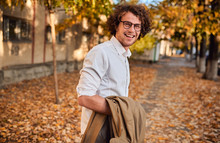 Horizontal Potrait Of Young Businessman With Glasses Posing Outdoors Going To The Lunch. Male Student In Autumn Street. Smart Guy In Casual Wears Spectacles With Curly Hair Walking Down The Street