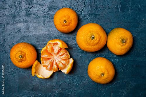 Fresh ripe mandarins on the textured navy blue table