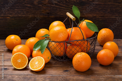 fresh orange fruits in a basket on wooden table
