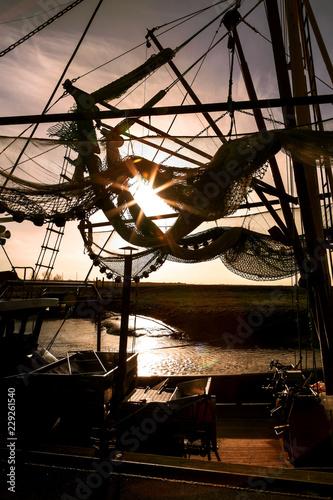 Krabbenkutter an der Nordseeküste im Gegenlicht, Fischernetz vor Abendhimmel