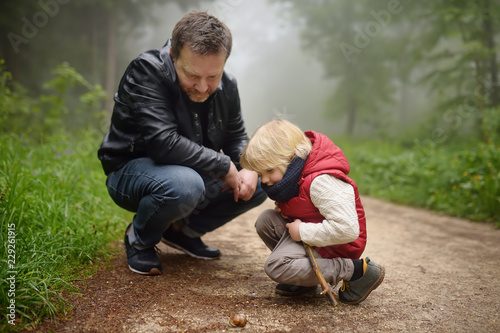 Fotografía  Little boy and his father looking on big snail during hike in forest