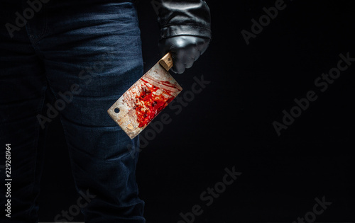 Photo Serial killer's hand with bloody meat cutter and black gloves