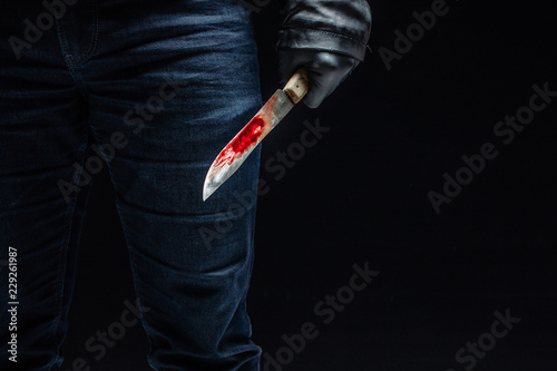 Serial killer's hand with bloody knife and black gloves Canvas Print