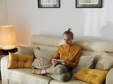 Woman Relaxing On Sofa With Tablet