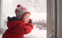 Baby Looking At Snow From Window