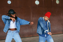 Portrait Of Cool Couple Wearing Denim Clothes Dancing On The Street.