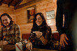 A young woman smiles and reads a note with friends in a cabin in upstate New York