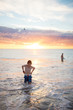 Boy and father swimming at the beach at sunset
