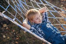 Cute Blond Boy Laying At Hammock Outdoors