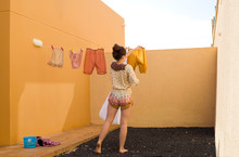 Young Woman Hanging Clothes On...