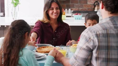 family praying around table - 500×281