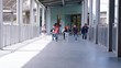 Elementary school kids run to camera in school corridor