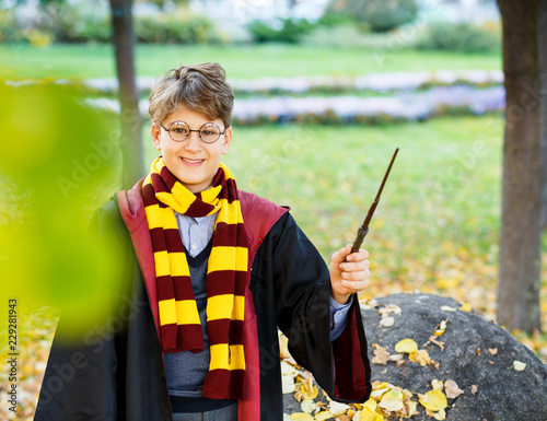 cute boy in glasses stands in autumn park with gold leaves, holds wand in his hand, wears in black suit and striped scarf. Halloween costume