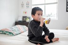 Asian Kid Using Asthma Inhaler...