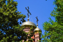Dome Of The Orthodox Church With Crosses, View Through The Branches Of Trees Against The Blue Sky