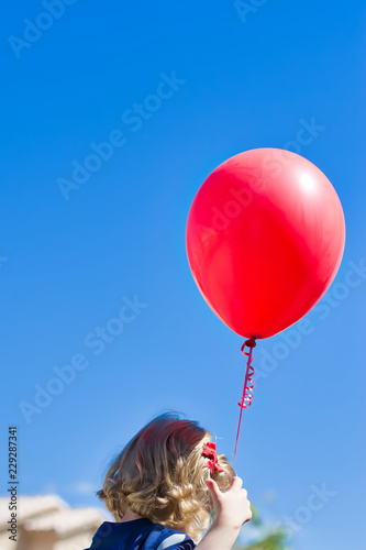 Photo  Little blonde girl with red bow in her hair holding a red latex helium balloon