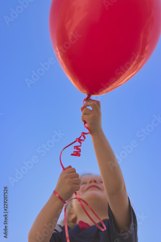 Photo  Little girl looking up with arms extending upward holding a red latex helium bal