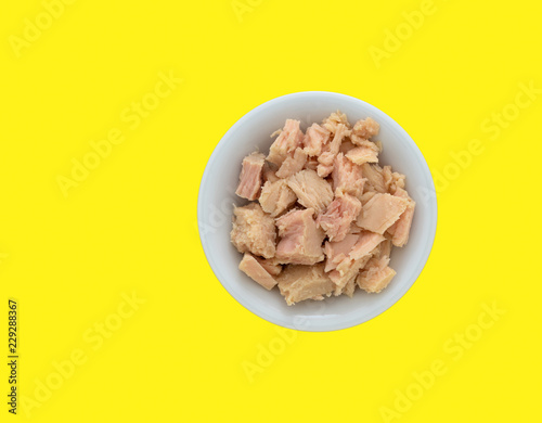 Top view of a bowl filled with solid white albacore tuna in olive oil chunks on a bright yellow background Canvas Print