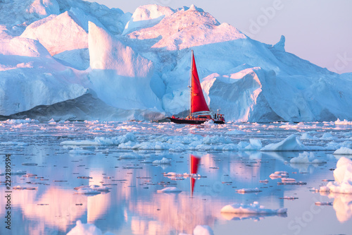 Little red sailboat cruising among floating icebergs in Disko Bay glacier during midnight sun season of polar summer Canvas-taulu