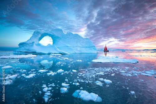 Fototapeta Little red sailboat cruising among floating icebergs in Disko Bay glacier during midnight sun season of polar summer