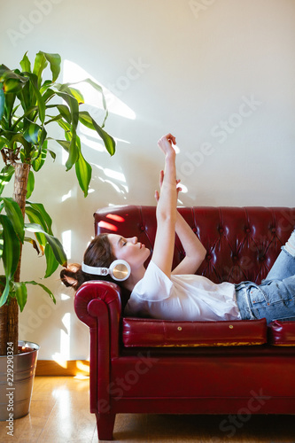 Young woman resting on sofa listening music on headphone.