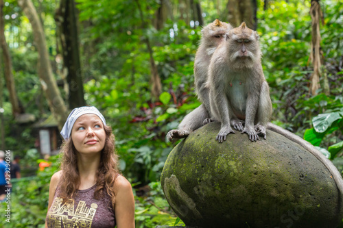 Tuinposter Aap Young Caucasian woman posing for a photo with cute monkey on shoulder. Curious macaque approaches traveler girl by jumping on her shoulder. Happy woman taking a fun photo with small monkey.