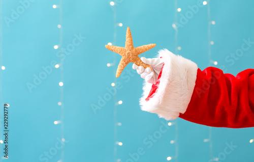 Photo Santa holding a starfish on a shiny light blue background