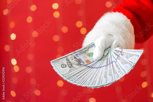 Fotografía  Santa holding US dollar bills on a shiny light red background